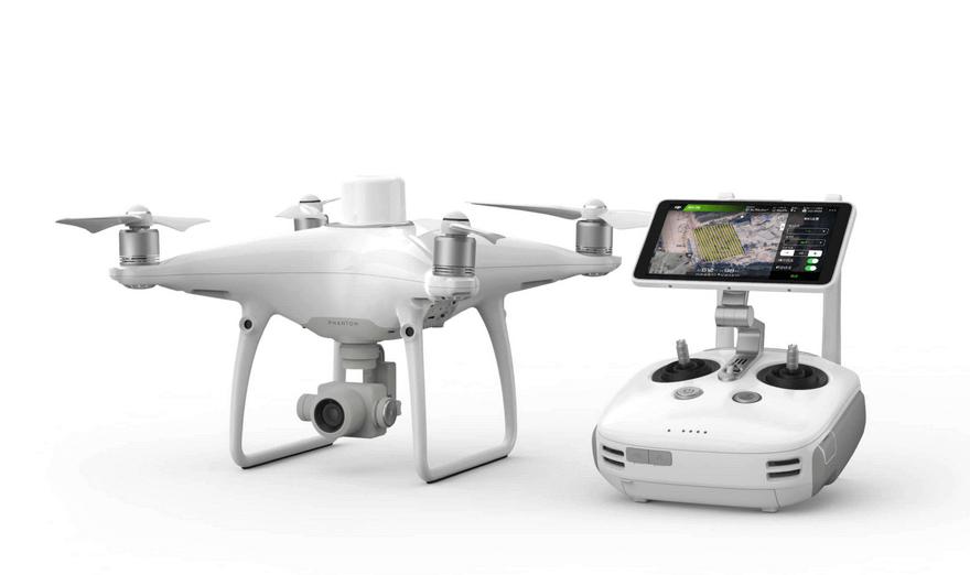 nowoczesny dron DJI Phantom 4 RTK zzamontowaną kamerą obok kontrolera