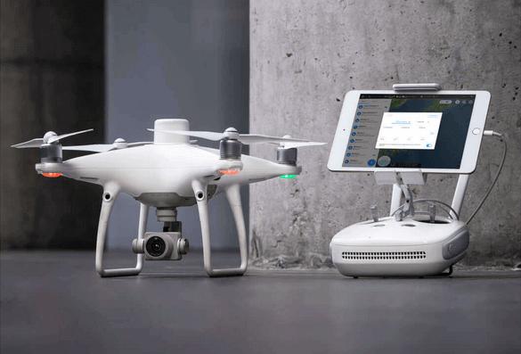 dron DJI Phantom 4 RTK obok operatora nabetonowej posadzcce