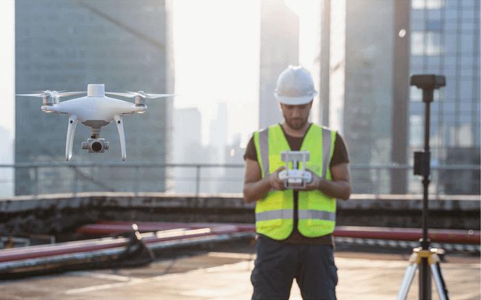 dron DJI Phantom 4 RTK podczas pracy obok operatora