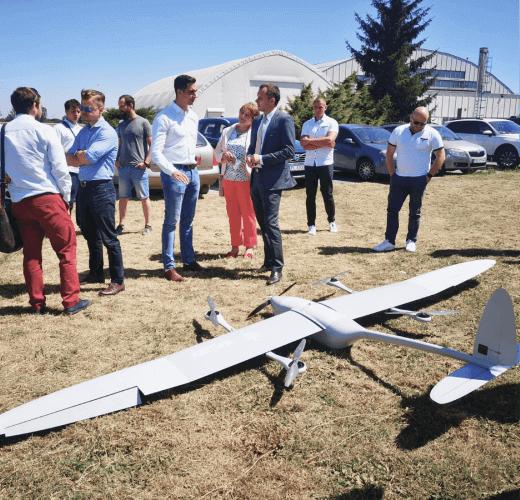 inspekcje dronami grupa ludzi przy dużym modelu samolotu bezzałogowego