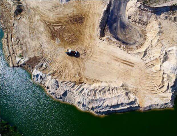 drone surveying - a photo of an open-pit mine surrounded by water